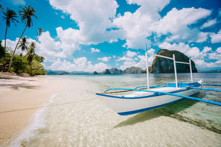 Impressive white cloudscape above picturesque sea shore with boat in El Nido, Palawan, Philippines. Wonderful nature Stok Fotoğraf