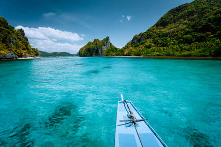 Boat trip to tropical islands El Nido, Palawan, Philippines. Steep green mountains and blue water lagoon. Discover exploring unique nature, journey to paradise.