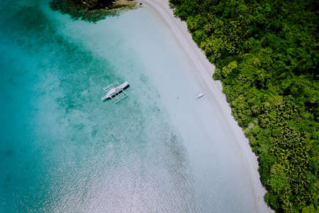 Aerial drone view of the beautiful paradise lagoon and white sand beach. Local boats on the surface. Summer exotic vacation concept
