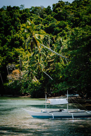 Palawan El Nido Marine Reserve Park famous nature spot blessed ecosystem rainforest surrounds incredible white sand beaches with local boat resting in the shadow