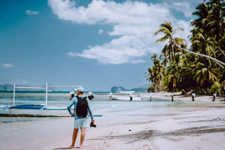 Back view of the man photographer with camera on pristine beach. Travelling tour most beautiful photo locations spots in Asia: El Nido, Palawan Island, Philippines