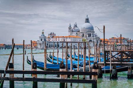 Venice view on Santa Maria della Salute basilica and gondolas on the Grand canal. Famous tourist attraction, summer city trip