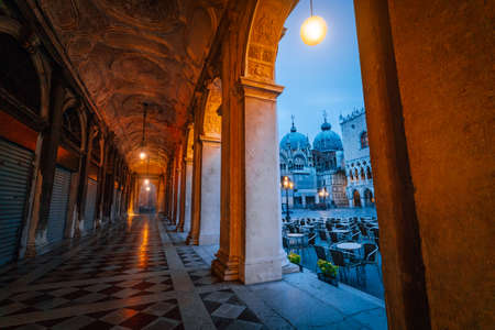 Evening view of Basilica di San Marco and Campanile through the street arch hallway on San Marco in Venice, Italy. Cityscape of Venice at dawn, blue hour