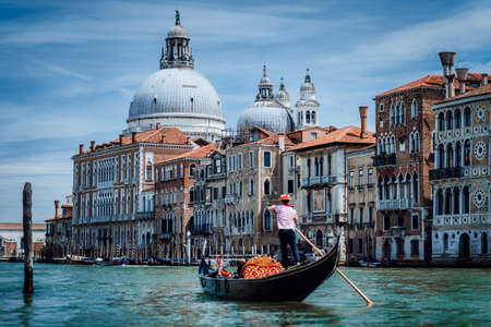 Traditional Gondola and gondolier on Canal Grande with Basilica di Santa Maria della Salute in the background in Venice, Italy. Summer vacation city trip