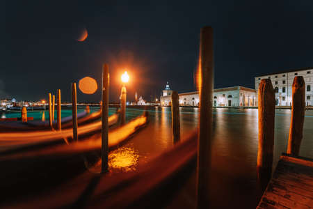Amazing night urban landscape from Venice city canal with gondolas anchored on Grand Canal in Venice - long exposure night shot with motion blurred gondolas