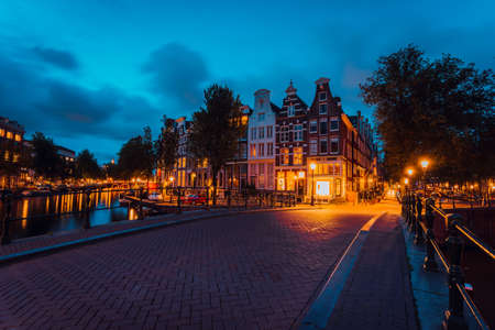Amsterdam illuminated bridge with typical dutch houses in evening blue hour lights, Holland, Netherlands