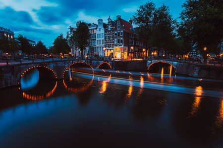 Bridge illumination and boat light trails in evening Amsterdam with reflection in Herengracht canal. Typical dutch houses in dusk light, Holland, Netherlands Stok Fotoğraf