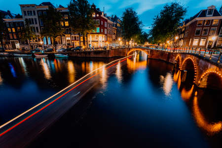 Amsterdam evening illuminated down town city. Touristic boat light trails and bridge reflections at the Leidsegracht and Keizersgracht canals. Long exposure shot. City trip visiting concept Stok Fotoğraf