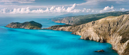 Panorama scenery view of Assos peninsula and coastline in Kefalonia Greece. Turquoise calm mediterranean water impressive white clouds