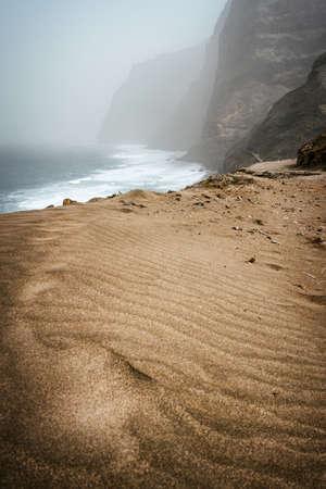 Santo Antao, Cape Verde - Cruzinha da Garca. Mountain moody coastline and Atlantic ocean waves. Sandy dune in foreground Stok Fotoğraf