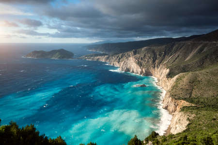 Dreamy atmosphere on picturesque jagged coastline of Kefalonia. Overcast weather, deep clouds, stormy sea and sunlight, Cephalonia, Ionian islands, Greece