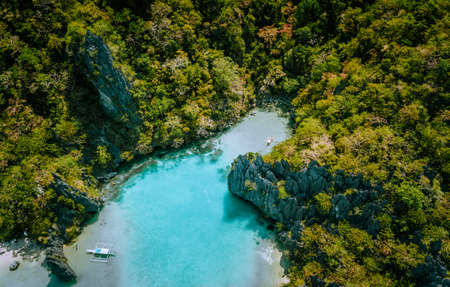 Aerial drone view of blue turquoise transparent lagoon water of tropical island with rugged steep mountains rocks, jungle and sandy beaches