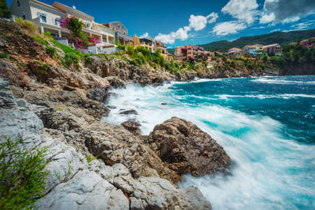 Long exposure of picturesque mediterranean Assos village, Kefalonia island Greece. Colorful houses at the rocky shore. Summer vacation travel