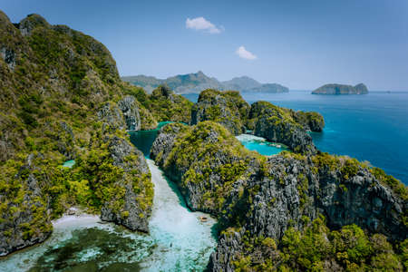 Aerial drone view of turquoise big and small lagoons surrounded by steep rocks, Marine National Reserve in El Nido, Palawan