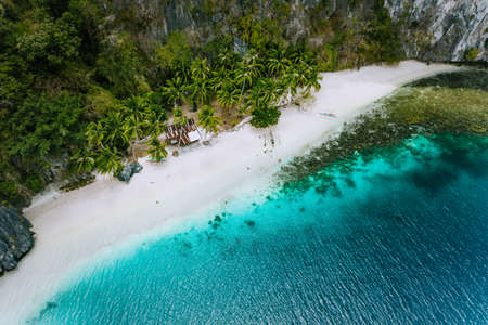 Aerial drone view of abandoned house hut on Pinagbuyutan Island in El Nido. Amazing white sand beach and emerald lagoon water Stok Fotoğraf
