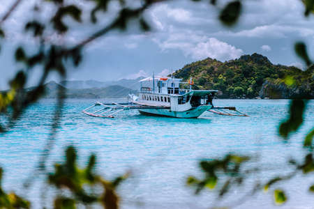 Tourism divers boat in blue cadlao lagoon framed by leaves. Island hopping tour, El Nido, Palawan, Philippines Stok Fotoğraf