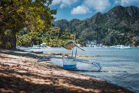 Bangka fishing boat on shore with El Nido village in background, Palawan, Philippines
