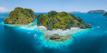 Aerial drone view of tropical Shimizu Island steep rocks and white sand beach in blue water El Nido, Palawan, Philippines. Tourist attraction most beautiful famous nature spot Marine Reserve Park