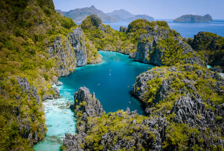 El Nido, Palawan, Philippines. Aerial drone view of beautiful big lagoon surrounded by karst limestone cliffs. Tourists explore area on kayaks