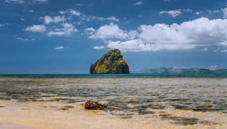Panoramic low angle shot of beautiful secluded cliff island in open ocean surrounded by turquoise blue ocean water. Bacuit archipelago, El Nido, Palawan