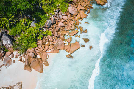 Aerial drone view of tropical paradise like beach with pure crystal clear turquoise water, bizarre granite rocks and coconut palm trees. Travel concept Stock fotó