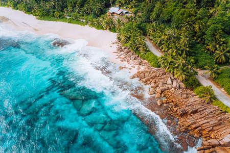 Aerial view of tropical dreamy beach Anse Bazarca, Mahe island, Seychelles. White powdery sand, azure water, lush vegetation, granite rocks Фото со стока