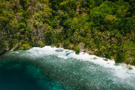 Aerial drone view of a secluded deserted tropical beach with lonely tourist boat surrounded by rainforest jungle. Cadlao Island, El Nido, Palawan
