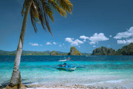 El Nido, Palawan, Philippines. Lonely filippino banca boat moored in turquoise ocean water. Island hopping tour with beautiful tropical scenery
