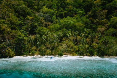 Palawan, Philippines, El Nido. Aerial drone view of a secluded deserted tropical beach with lonely tourist boat in frost of impressive rainforest jungle