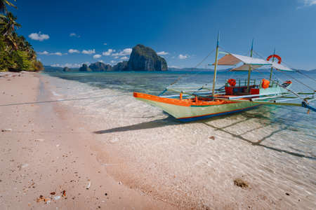 Tourist banca boat on beach ready for island hopping with beautiful scenery of surreal Pinagbuyutan island in background. Exotic nature scenery in El Nido, Palawan, Philippines. Stock Photo