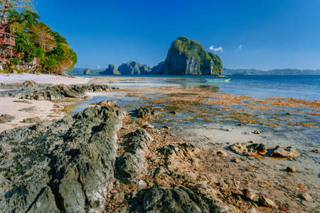 Rocky exotic coastline in front of Pinagbuyutan island. Dreamlike landscape scenery at El Nido, Palawan, Philippines.
