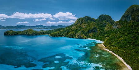Aerial drone panoramic view of uninhabited tropical island with rugged mountains, rainforest jungle and big blue bay with shallow ocean water.