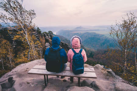 Young couple in outdoor clothing with backpacks sitting and rest on bench enjoying view of mountain ridge, forest and river in the valley on hiking trail. Travel lifestyle concept