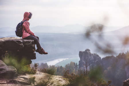 Young woman in outdoor clothing with backpack sitting on cliffs edge enjoying view of mountain ridge, forest and river in the valley. Travel lifestyle concept