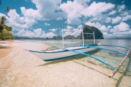 El Nido, Palawan, Philippines. White banca boat on sandy beach with crystal clear water ready for island hopping trip. Amazing Pinagbuyutan island in background. Beautiful landscape scenery Banco de Imagens