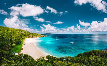 Grand Anse beach at La Digue island in Seychelles arial panoramic view. White sandy beach with blue ocean lagoon and catamaran yacht moored