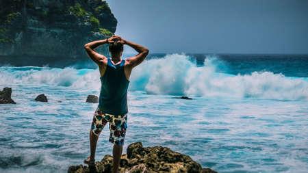 Man Provoke Ocean Waves on Tembeling Coastline at Nusa Penida island, Bali , Indonesia Stock Photo