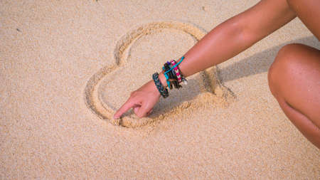Female hand draw on the sand near the sea heart. Banque d'images - 137181371