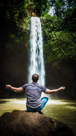 Man meditating in front of waterfall near Ubud, Bali, Indonesia. Banque d'images