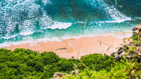 Aerial view of rolling turquoise ocean waves over pure clear sandy beach on sunny day. Surrounded by lush green jungle Banco de Imagens