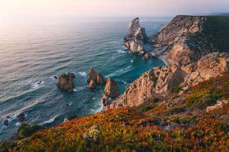 Praia da Ursa. Sintra Region. Portugal. Ursa Beach scenic seascape with sea stacks and cliffs in evening sunset light on Atlantic Ocean coast. 写真素材