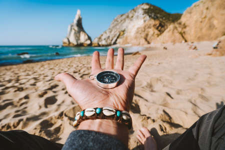 Compass in the open hand symbolling adventure-seeking concept against Ursa beach, Sintra, Portugal
