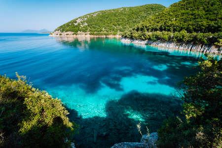 Azurblaue Bucht. Malerische Landschaft der Bucht mit türkisfarbenem ruhigem Wasser, umgeben von Hügeln mit Zypressen, Pinien und Olivenbäumen. Weiße Kalksteinfelsen spiegeln sich im kristallklaren Wasser.