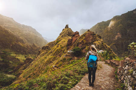 Santo Antao Island Cape Verde. Tourist girl with backpack walking down along the trekking route to verdant Xo-Xo valley between mountain peaks.