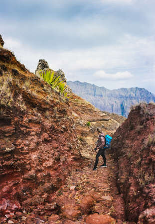 Female hiker with blue backpack staying on the stony cobbled trekking trail leading down to the Paul valley between barren mountain peak on Santo Antao island, Cabo Verde.
