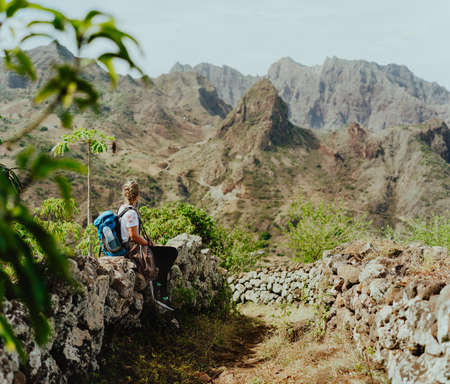 Santo Antao, Cape Verde. Woman tourist with backpack enjoying arid mountain ridge on hiking route to Coculi valley of Ribeira Grande