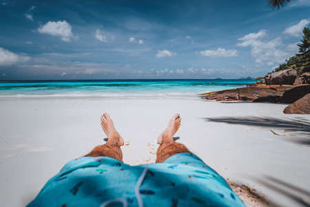 POV of male wearing swimming shorts with tanned legs on paradise white sand tropical exotic beach with view to turquoise blue ocean. Travel holidays vacation concept.