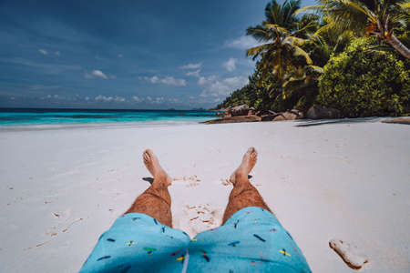 Male wearing swimming shorts with tanned legs on paradise white sand tropical exotic beach with view to turquoise blue ocean. Travel holidays vacation concept.