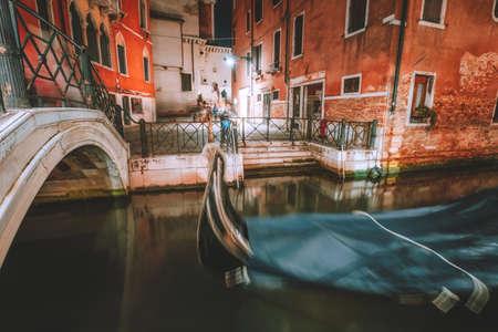 Venice Gondola boat in small channel with arch bridge in lagoon city Venice at night time. long exposure Venezia Italy