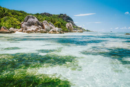 La Digue island, Seychelles. World famous paradise beach Anse Source d'Argent with shallow lagoon, granite boulders.
